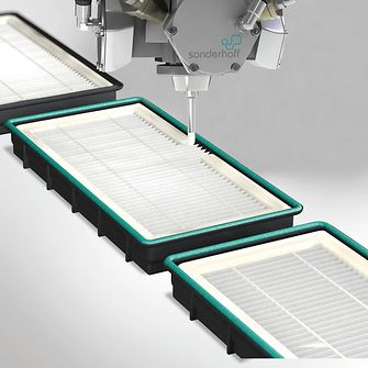 The mixing head of the dosing system applies Fermadur foamed adhesive sealant along the filter frame contour for bonding and sealing pleated filters.